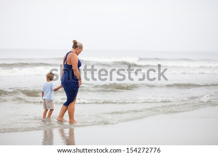 Mother and son walk holding hands in shallow waters of ocean along beach coastline