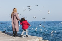 Mother and son walk to the seaside. Birds flying above the water. Cold season vacations