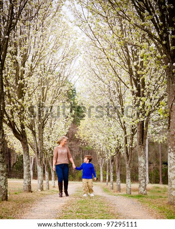 Mother and son walking hand in hand  at park during spring
