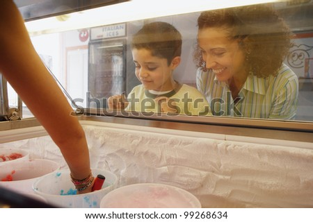Mother and son watching through ice cream case window