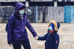 Mother and son wearing face mask at street. Prevention coronavirus. Coronavirus quarantine. People prevent infection from corona virus. Coronavirus outbreak, lockdown. Family going home.