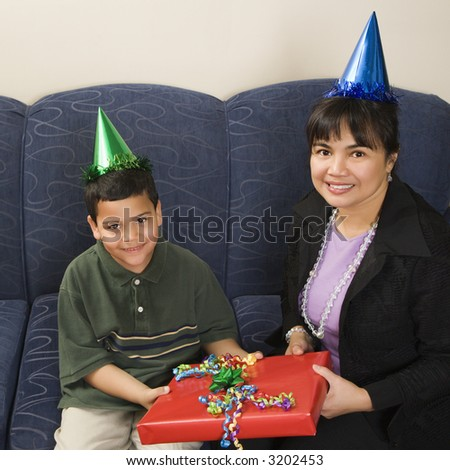 Mother and son wearing party hats holding birthday presents smiling and looking at viewer. - stock photo
