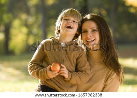Mother and son with apple outdoors
