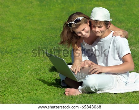 mother and son with notebook on the grass