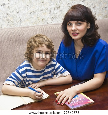 Mother and sun, schoolboy eight years, European, preparing school lessons at home.