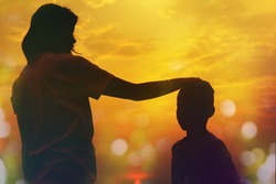 Mother and sun silhouettes at sunset with blur nature bokeh background