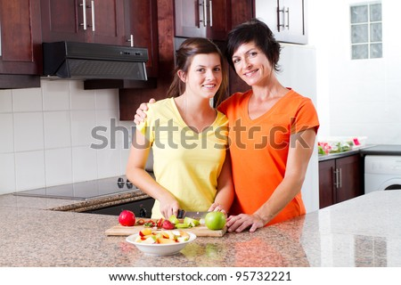 mother and teen daughter making fruit salad in kitchen