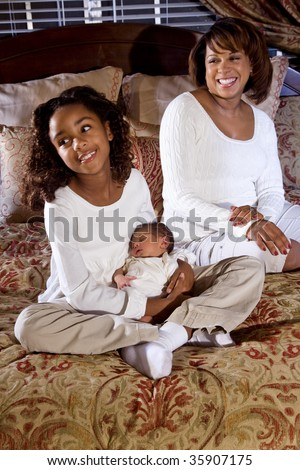 Mother and ten year old daughter with newborn baby