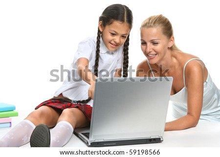 Mother and the daughter cheerfully using computer in studio