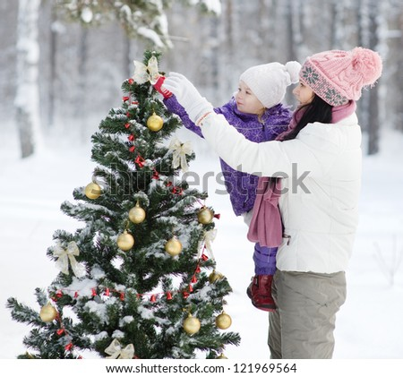 mother and the daughter decorate a Christmas tree