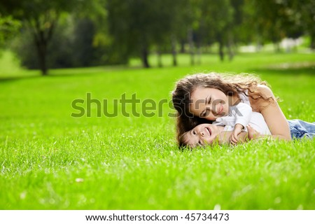 Mother and the small son lie on a summer lawn