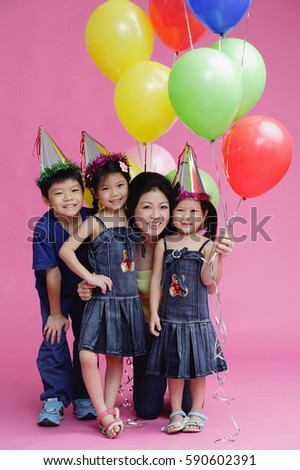 Mother and three children, posing with balloons