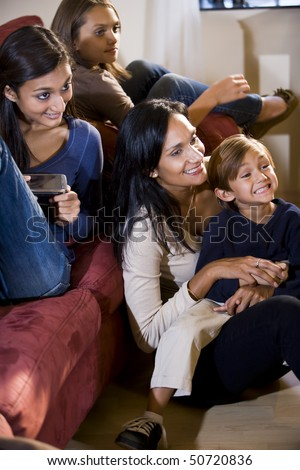 Mother and three children sitting together on living room sofa watching television