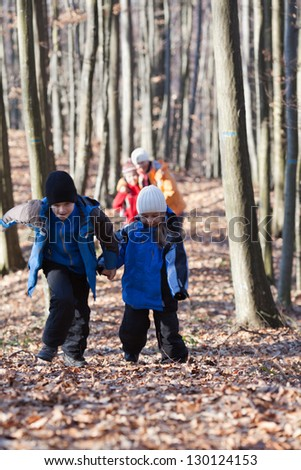 Mother and three children walking in the woods