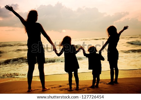 Mother and three kids silhouettes standing on beach at sunset