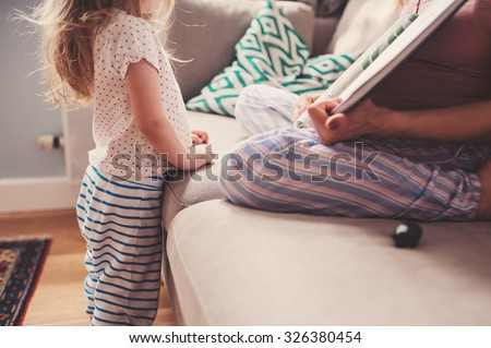 mother and toddler daughter reading book at home