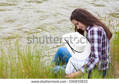 Mother and toddler son sitting by the riverside - stock photo