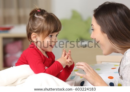 Mother and toddler wearing red shirt playing together on a bed in the bedroom at home