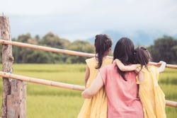 Mother and two asian little child girls looking at beautiful nature in the cornfield together in vintage color tone