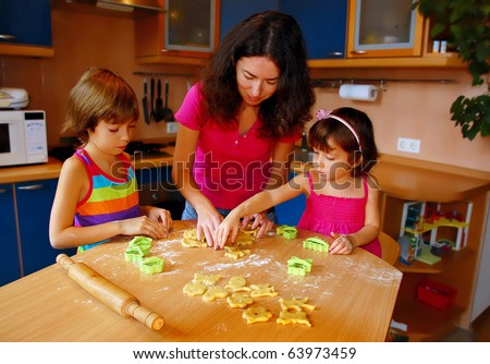 Mother and two daughters baking together in kitchen