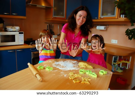 Mother and two daughters baking together in the kitchen