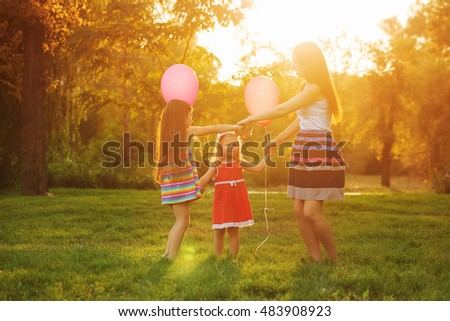 Mother and two daughters dance in a circle holding hands. Family time together. Cheerful picnic. Girls with balloons. #483908923