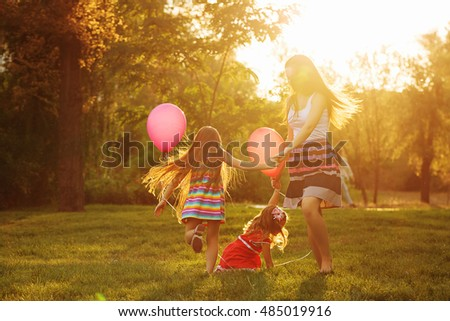 Mother and two daughters holding hands circling. Family time together. Cheerful picnic. Girls with balloons. Soft focus #485019916