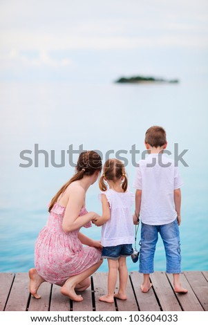 Mother and two kids at wooden dock enjoying ocean view