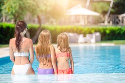Mother and two kids enjoying summer vacation in outdoors swimming pool