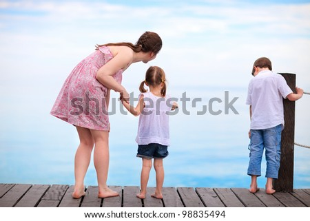 Mother and two kids  looking for fish from wooden dock