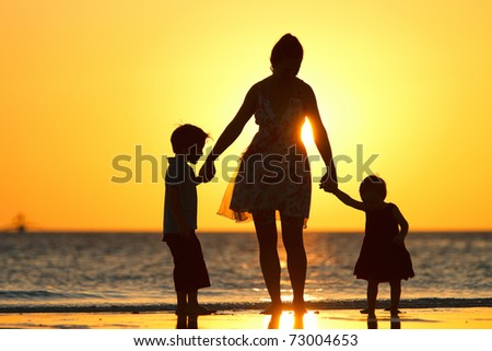 Mother and two kids silhouettes on beach at sunset