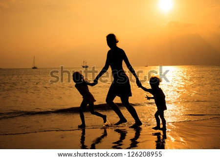Mother and two kids silhouettes running on beach at sunset