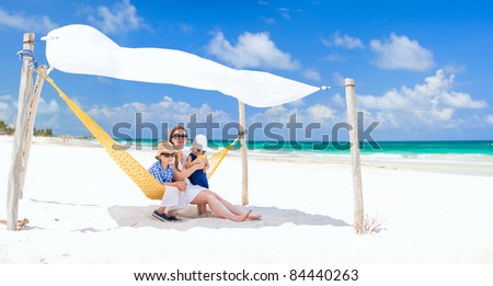 Mother and two kids sitting in hammock at tropical beach