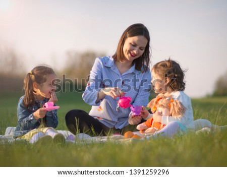 Mother and two little daughter playful with a dolls and plastic toy coffee cups. Funny picnic imitation,mother enjoys drinking fake coffee with hers daughters. Female part of the family outdoor. #1391259296