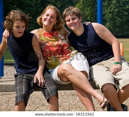mother and two sons horsing around on a playground bench
