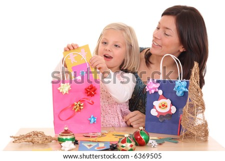mother and 5-6 years old girl making Christmas decoration /all decorations are made by mother and child/