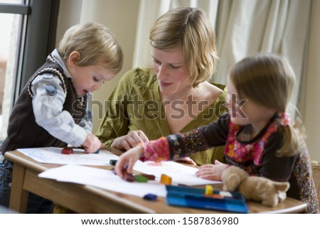 Photo of Mother and young children coloring