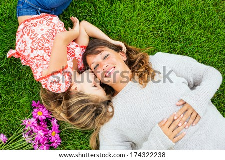 Mother and young daughter in the park relaxing on the grass, intimate moment - stock photo
