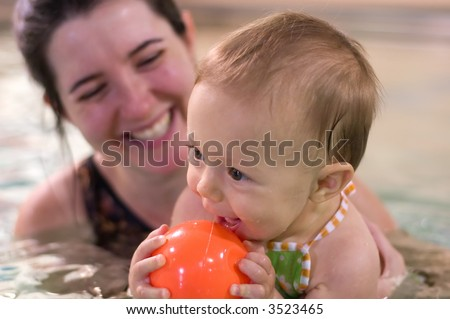 Mother and young daughter playing and having a great time during baby swimming lessons.