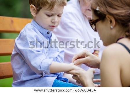 Mother applying band aid on scratch on son's arm while sitting on bench in park. Senior grandmother sitting beside on bench.
