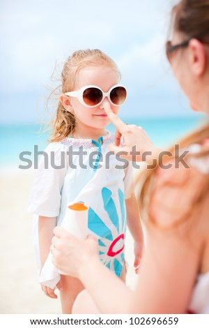 Mother applying sunblock cream on her daughters nose