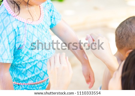mother applying sunscreen lotion on her daughter.sunscreen protection uv sun light on the beach.