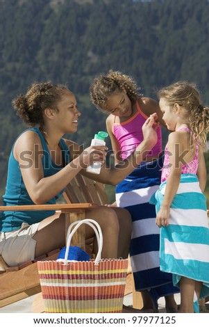 Mother applying suntan lotion to daughters at beach - stock photo