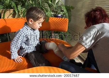 mother bandages a little boy's leg