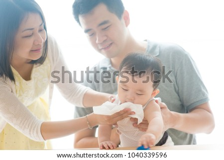 Mother blow baby nose with tissue paper. Asian family spending quality time at home, living lifestyle indoors.