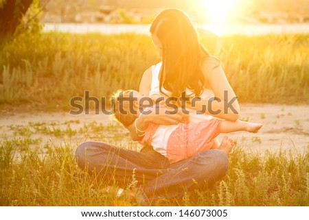 Mother breast feeding  baby in the sunlight at sunset. Summer holiday.