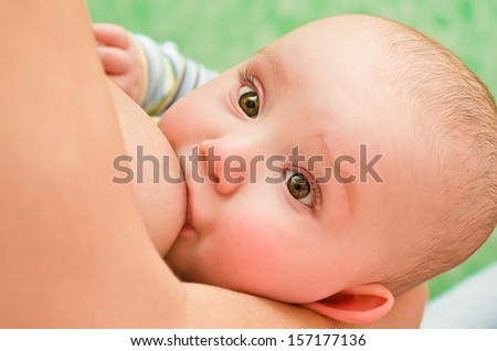 Mother breastfeeding her baby with breast milk