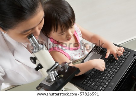 Mother busy working with microscope and her daughter busy playing laptop. focus mainly on little girl
