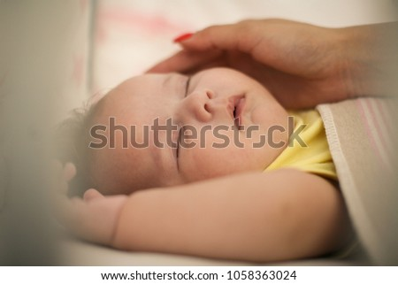 Shutterstock Mother caressing her baby.