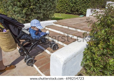 Mother carries a stroller down the stairs in garden without ramp for the disabled and baby prams  #698254723